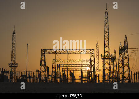 A sunrise photo through sand in the air. Photo of a power sub-station in Bahrain, Middle East. - Stock Photo