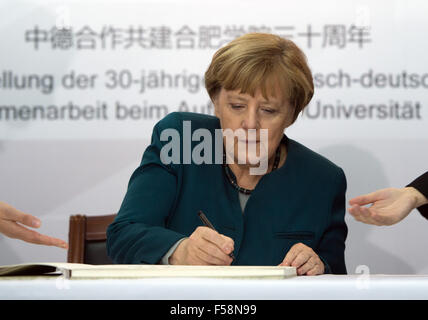 Hefei, China. 30th Oct, 2015. German Chancellor Angela Merkel signs the guestbook as she visits the German Academy - Stock Photo