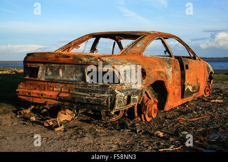 a rusty abandoned car on the shore - Stock Photo