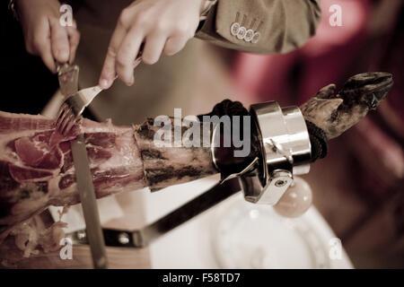 Color artistic digital rectangular horizontal photo of the hands of a man tcutting a leg of Spanish hand cut Iberian - Stock Photo