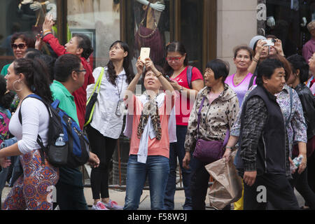 Tourists constsntly snap photos on their phones in Times Square, New York City. - Stock Photo
