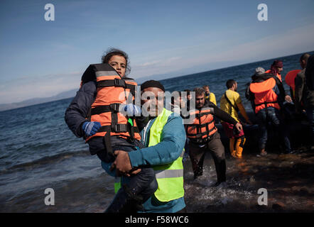 Lesvos, Greece. 30th Oct, 2015. Volunteer Khalid Mehmood, 48, from Bolton near Manchester in the UK helps a girl - Stock Photo