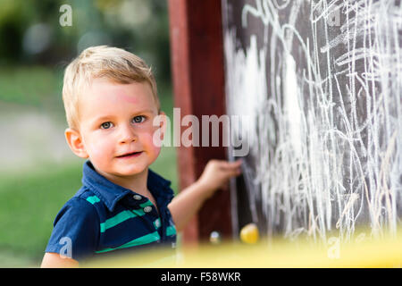 Creative cute toddler drawing with chalk outdoors - Stock Photo