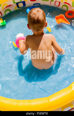 Toddler playing with his toys in a pool outdoors during summertime - Stock Photo