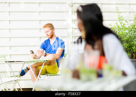 Beautiful black woman looking towards a handsome man in a cafe outdoors - Stock Photo
