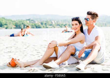 Romantic young couple in love sitting at a sandy beach and smiling - Stock Photo