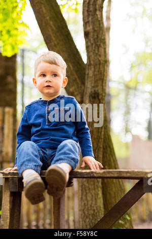 Little handsome boy sitting on a bench in the park - Stock Photo