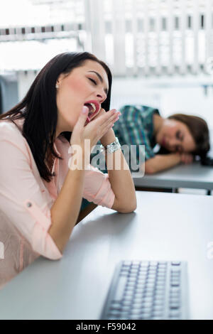 Young beautiful girl yawning during class from boredom and fatigue - Stock Photo