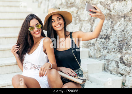 Friends taking selfie of themselves during summertime - Stock Photo