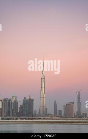 Skyline of skyscrapers and Burj Khalifa tower before sunrise in Dubai United Arab Emirates - Stock Photo