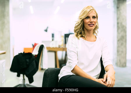 Beautiful blonde businesswoman sitting in an office with legs crossed - Stock Photo