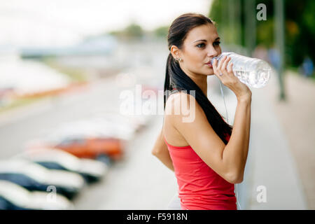 Thirsty woman drinking water to recuperate after jogging - Stock Photo