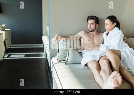 Lovely couple relaxing at a wellness center, laying in a rob and towel - Stock Photo