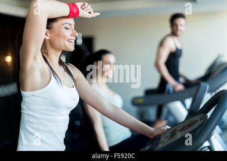 Young, beautiful woman training by riding a bicycle in a gym and sweating - Stock Photo