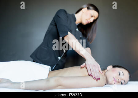 Young beautiful massage therapist massaging a stunning young lady laying with her chest on the massage table - Stock Photo
