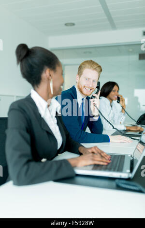 A beautiful, black, young woman working at a call center in an office with her red haird colleague talking to a - Stock Photo