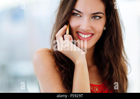 Beautiful model calling on phone and smiling - Stock Photo