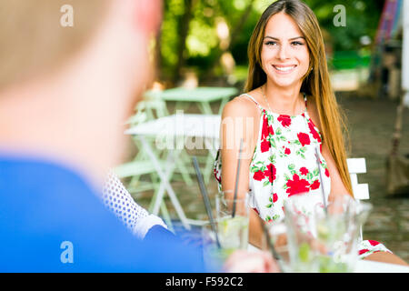 Beautiful woman and a handsome man flirting dating while sitting at a table in a cafe - Stock Photo