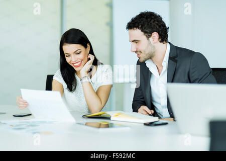 Beautiful businesswoman and a handsome businessman discussing in a modern office - Stock Photo