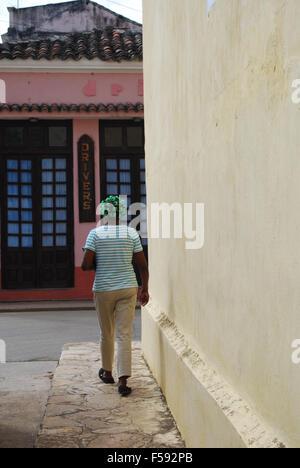 A cuban woman in hair curlers walking along a street in Remedios, Cuba - Stock Photo