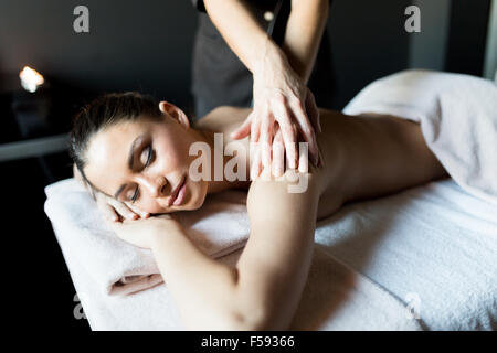 Beautiful, young and healty woman having her shoulder and body massaged by a professional masseur at a spa center - Stock Photo