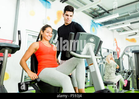 Beautiful young woman instructed by a handsome man in a gym while using a bicycle - Stock Photo