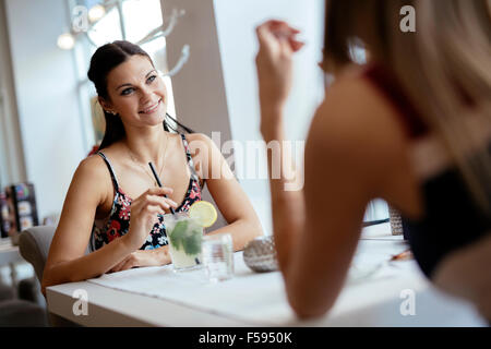 Beautiful women enjoying beverages in cafe and talking - Stock Photo