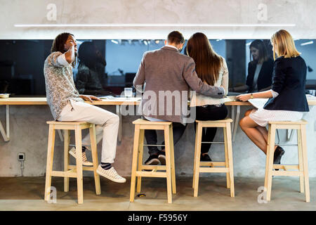 Group of people having a break from work in the cafeteria - Stock Photo