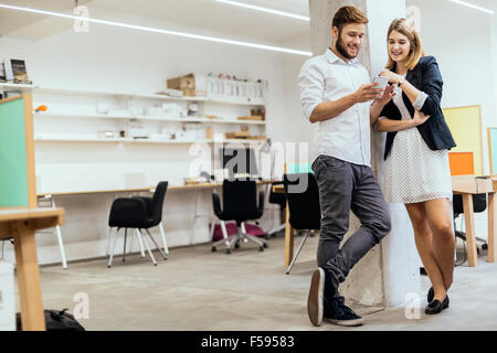 Creative smart colleagues in office using phones and smiling - Stock Photo
