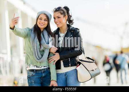Two young women taking a selfie of themselves - Stock Photo