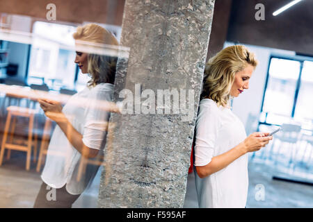 Beautiful woman using mobile phone to write message - Stock Photo