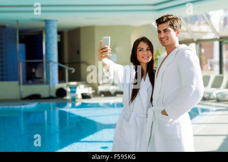 Couple in love standing next to a  pool in a  robe and relaxing - Stock Photo
