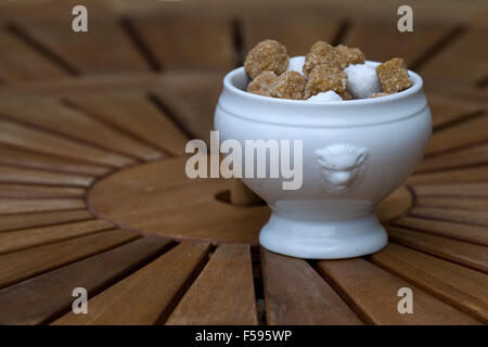 Brown and white sugar cubes in a ceramic bowl on a round wooden table - Stock Photo