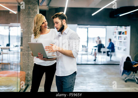 Business coworkers discussing new ideas and brainstorming in a modern office - Stock Photo