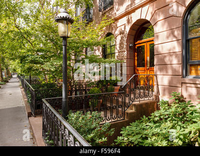 Chelsea tree-filled street and its townhouses and frontyards, Manhattan, New York City - Stock Photo