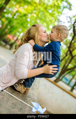 Beautiful young mother with her handsome little son in a park - Stock Photo