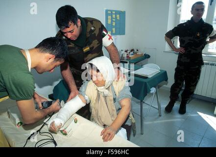 war crisis in Kosovo, april 1999, a woman receives medical cures in field hospital of the mountain brigade Taurinense - Stock Photo
