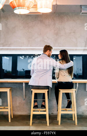 Handsome man hugging a beautiful woman in a bar - Stock Photo