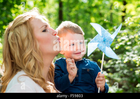 Beautiful women is blowing a paper windmill with her little son - Stock Photo