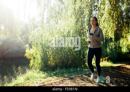 Sporty girl jogging in park close to a river - Stock Photo