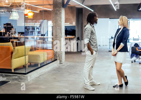 Colleagues smiling and talking in a beautifully designed office - Stock Photo