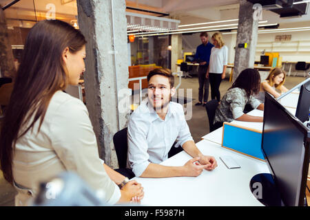 People working at busy modern office in front of computers - Stock Photo
