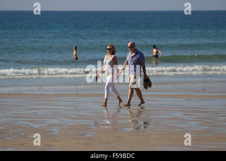 Attractive mature couple walking on beach beside the sea St Ouen's beach Jersey The Channel Islands - Stock Photo