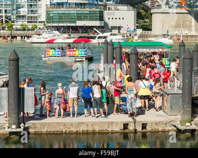 Passengers awaiting aquabus False Creek ferries at Granville Island dock on Canada Day, 1 July 2015. - Stock Photo