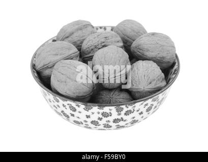 Walnuts in shells, in a porcelain bowl with a floral design, isolated on a white background  - monochrome processing - Stock Photo