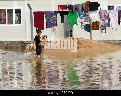 Baghdad, Iraq. 30th Oct, 2015. A refugee boy walks in water at the Alkzenzanah camp in Baghdad, Iraq, Oct. 30, 2015. - Stock Photo