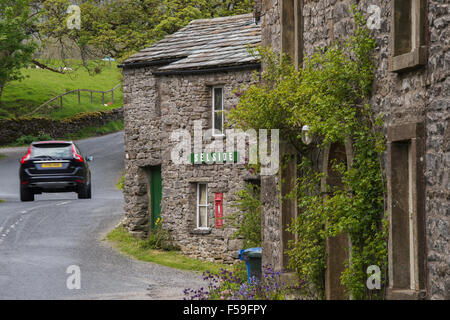 Car passes traditional, stone-built, roadside cottages  (name sign & post box) - quaint hamlet of Selside, Yorkshire - Stock Photo