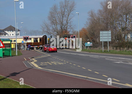 A Diesel shunter propelling a coach back into the Minehead station or yard with two cars waiting patiently at the - Stock Photo