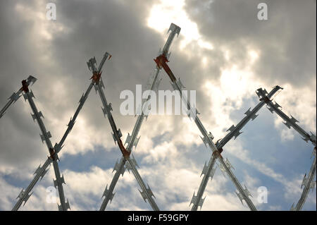 A line of diamond shaped razor wire metal fence set against a dramatic cloudy sky. - Stock Photo