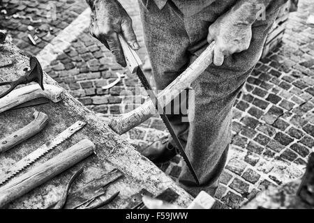 Old craftsman builds Hacksaw using the steel of old scythes. - Stock Photo